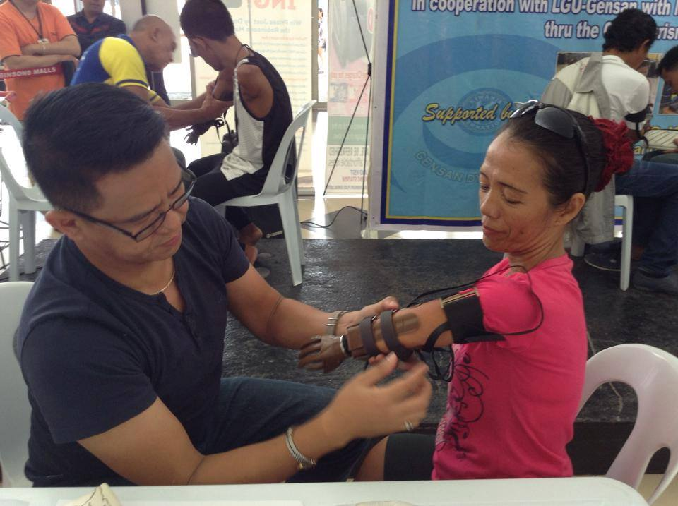 A recipient of a prosthetic hand is being assisted by a member of the foundation in general Santos City. Photo courtesy of IN-4 foundation.