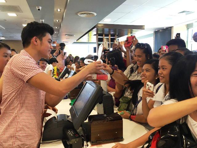 McDonald's celebrity influencer Iñigo Pascual assists a customer during the store opening.jpg